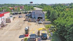 bird eye view of car wash with green trees on the right