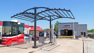 front view of car wash entrance with red booth on left and canopy above