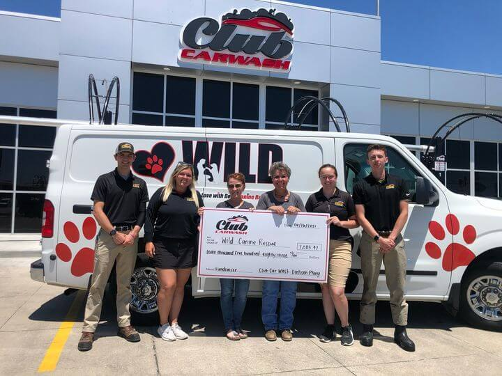 group of club car wash representatives with wild canine representatives holding check in front of wild canine vehicle