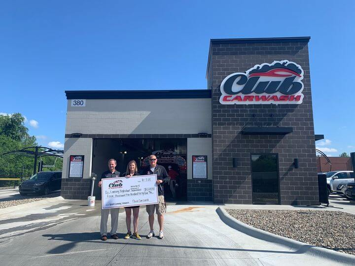 car wash employees and lansing high school representative holding big check in front of club car wash