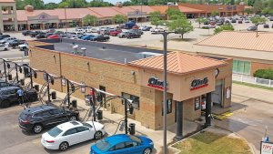 renovated tan building with parking lot on the left and shopping center in parking lot at top with club car wash logo building entry way