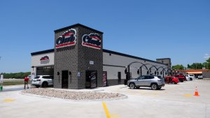 caddy corner ground view of car wash with free vacuums and parking lot to the right and car wash entrance to the left
