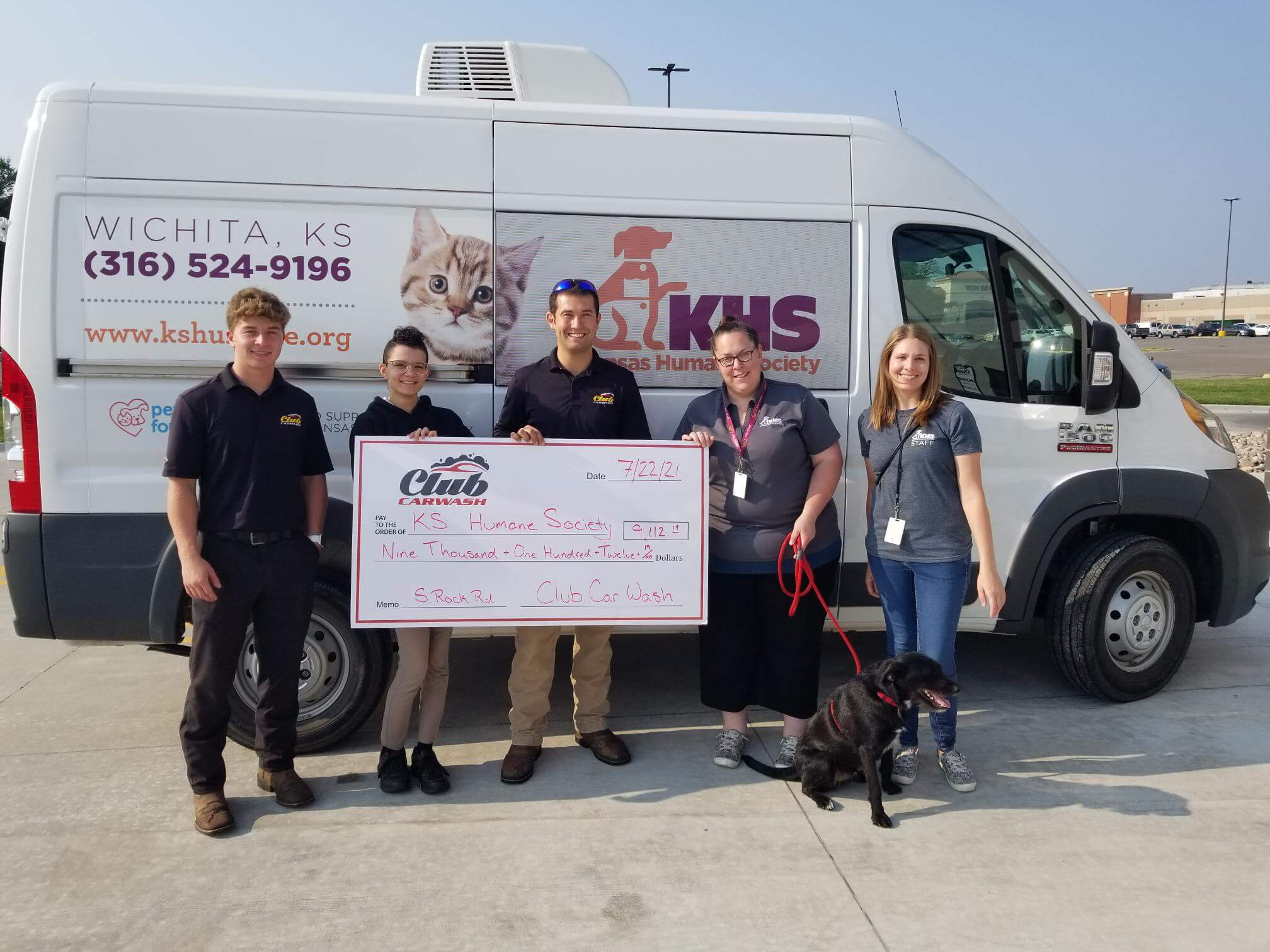 group of club car wash employees with kansas humane society representatives and dog with a check