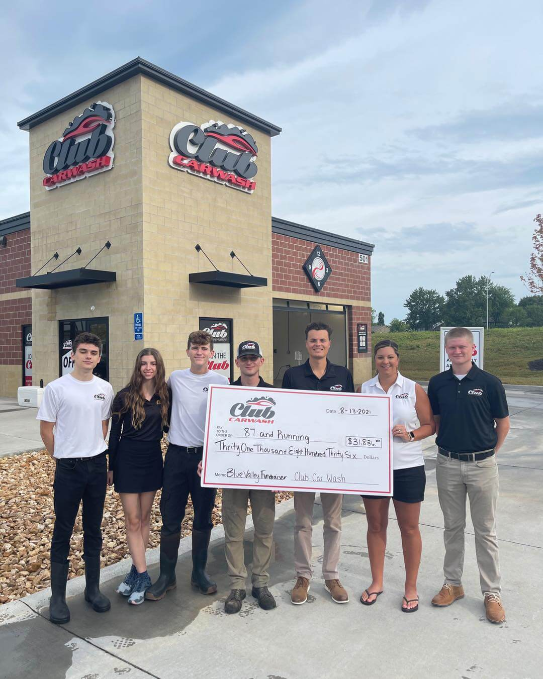 Check presentation with Club Car Wash employees holding check in front of a location.